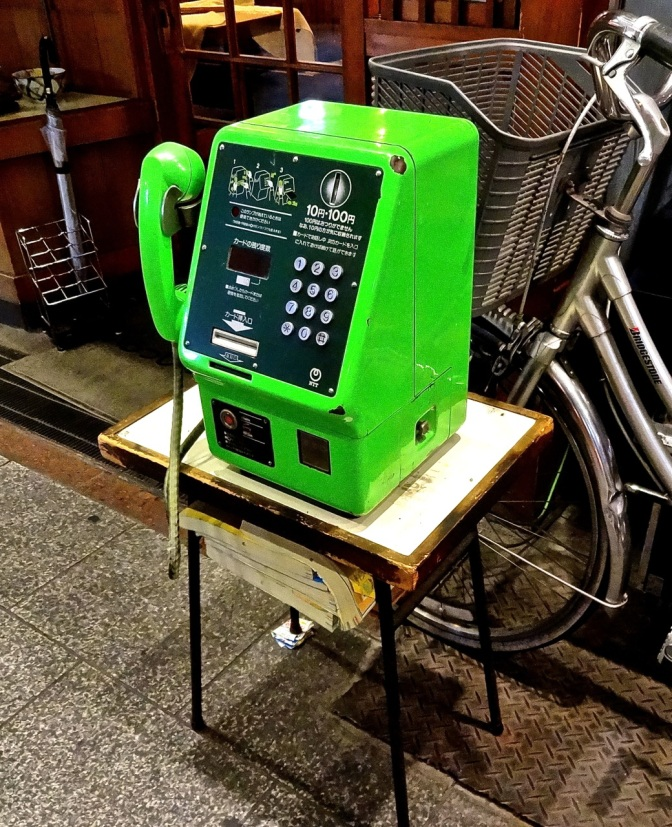 Although increasingly rare in the west, pay telephones still exist in many parts of Asia.  Often owned by small local companies, phones like this are set our daily in front of shops with the long bell wire trailing into the store behind it.