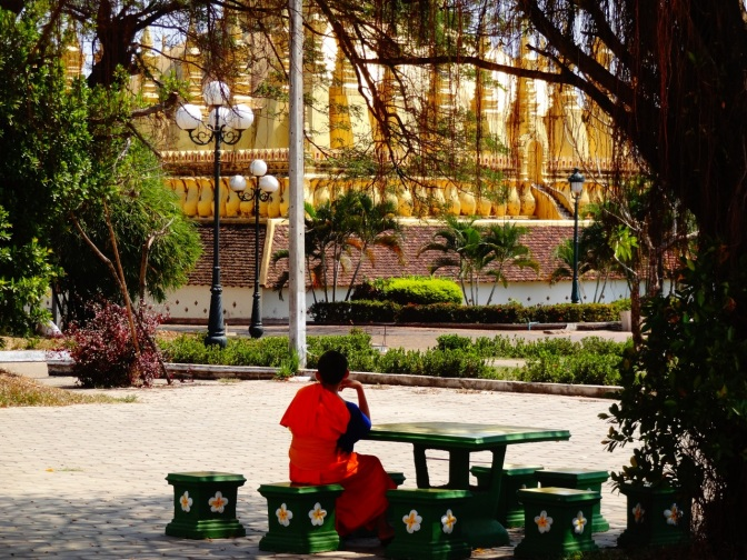 A young monk sits near the park at Patuxai monument.