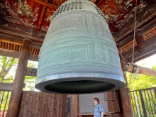 Alex seems about to be trapped by a giant thimble. One of the largest bells in Kyoto dwarfs him as he plots how to make it ring.