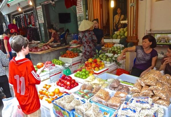 Alex haggles for an apple at the Hanoi street market.