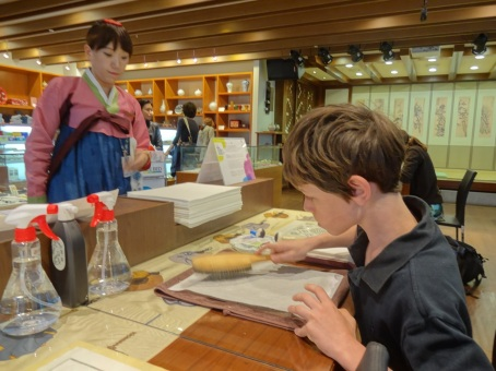 Alex makes a wood block ink print at the airport in Seoul.
