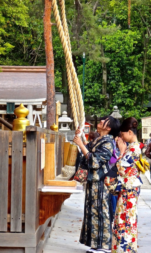 Buddhist stop to make an offering and ring a bell attached to a long cotton rope in front of one of Kyoto's many temples.