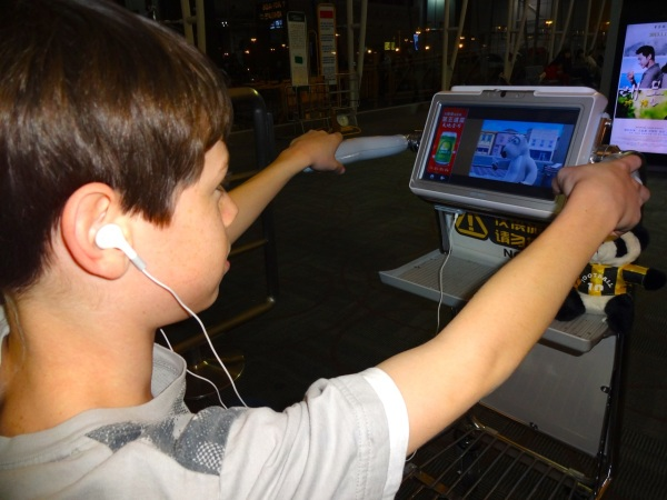 Keeping kids busy in an airport on a long layover is a challenge.  We have traveled through Guangzhou twice and Alex has discovered the free baggage cart/TV  set.  While often riding around the huge gate area, he can wirelessly watch movies and surf the web.
