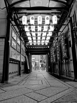Along one of the covered pedestrian-only streets in Kyoto, the entrance to a Buddhist temple is lit up with paper lanterns.