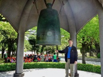 Kevin stands in front a large bell in the Hiroshima Peace Park.