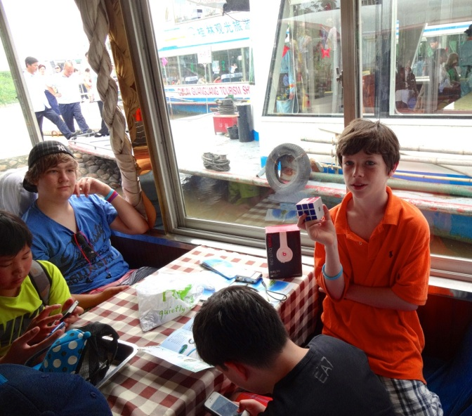 Below deck and just before departure at the marina in Gulin, Alex and his fellow middle schoolers keep busy with rubric cubes, cards and sadly electronics of all sorts.