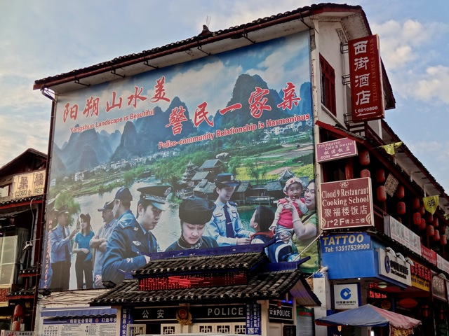 """Police-Community Relationship is Harmonious"". So says the huge sign on Yangshuo's West Street, just between Cloud 9 Restaurant and 7th Heaven Cafe above the tattoo shop."