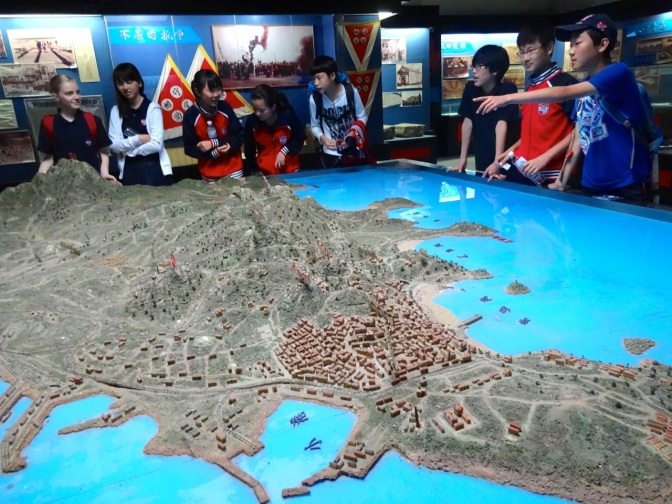 Students explore a scale model of the Qingdao area depicting the city during a siege of the city by British and Japanese forces in October and November 1914.