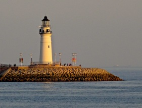 The last few minutes of the day's sun warm up the lighthouse at the end of the jetty near Qingdao's Olympic Sailing Center on the Yellow Sea.