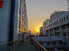 Looking east toward the rising sun over the Laoshan Mountains, the building that houses the Qingdao Amerasia International School catches the early light.