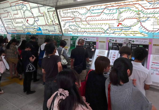 Commuters stand in quay to buy tickets for the Tokyo subway and the long distance trains that run in and out of the world's busiest train station.  Maps of the train system in Tokyo have been compared to dropping a large bowel of colored linguini on a piece of paper.