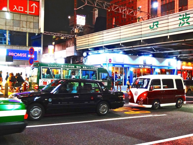 A VW microbus amid black cabs passes under a Japan Rail train passing overhead in Shibuya-Tokyo's and the world's busiest places.