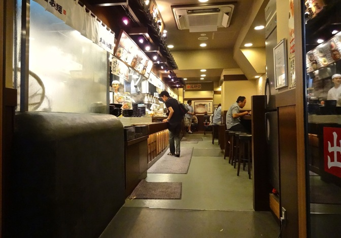 Steam covers the kitchen window of a sushi restaurant early on a Saturday night in Tokyo.