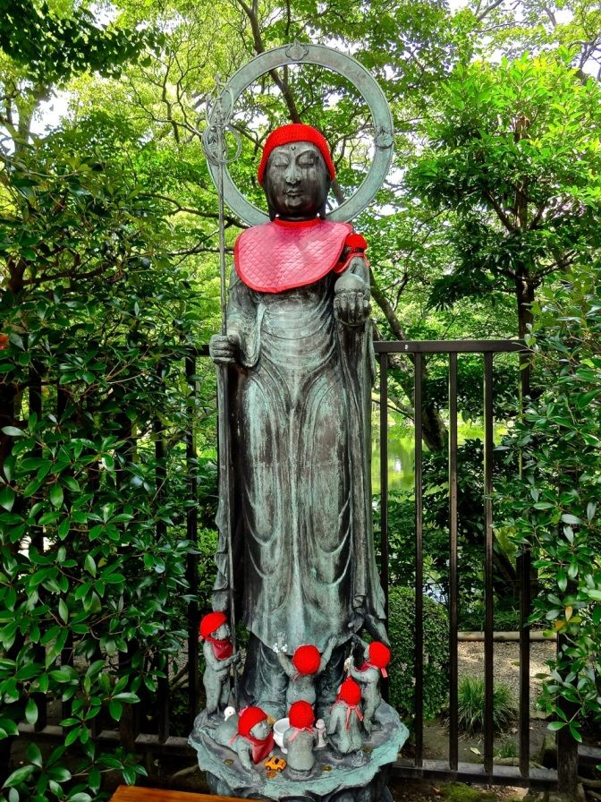 A brightly decorated statue, surrounded by lush gardens in a temple in Asakusa, is just steps from one of the most densely-populated cities in the world.