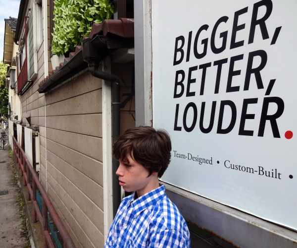 Alex poses under a sign along a side street in Tokyo.