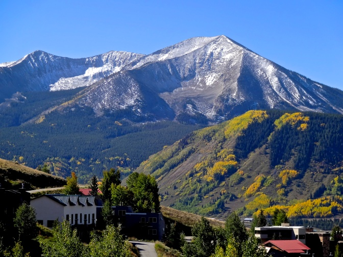 Snow, early and temporary in late September,  dusts the peaks on and around Crested Butte. The last of the annual golden canopy of aspen leaves glow in the warmer valleys below.
