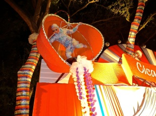 Inexplicably a costumed woman spins suspended overhead in a heart-shaped box (Nirvana reference?) during last years public New Year's Eve party in Thailand.