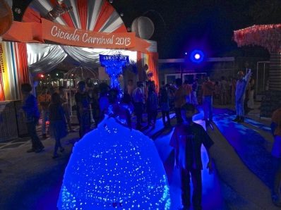 Alex stands next to a woman at the Orange Happiness New Year's festival, dressed in lighted neon blue dress.